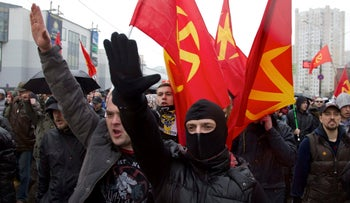 Nationalist demonstrators carry their flags and, some of them, raise their hands in a Nazi salute during a march to mark National Unity Day, in Moscow, Russia. Nov. 4, 2013