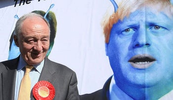 Britain's Labour candidate for London Mayor, Ken Livingstone stands in front of a poster depicting London Mayor Boris Johnson as an alien, to launch Labour's new Ad Bus in south London on April 30, 2012