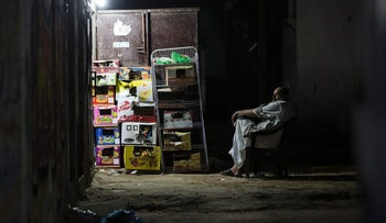A man sits outside his store in Gaza during the few hours of electricity daily, July 2017.