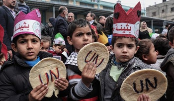 Palestinian children hold bread patties during a protest against aid cuts outside UN offices in the Gaza Strip.