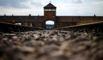In this June 25, 2015 file photo railway tracks lie in front of the main entrance of former Auschwitz-Birkenau Nazi death camp in Oswiecim, Poland