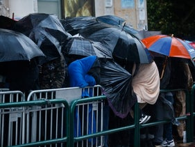 Asylum seekers stand in line in the rain at the Interior Ministry in Tel Aviv.