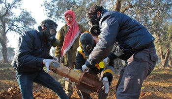 Members of the civil defense remove the remnants of a rocket reportedly fired by regime forces on the outskirts of the rebel-held besieged Syrian town of Douma, February 1, 2018.