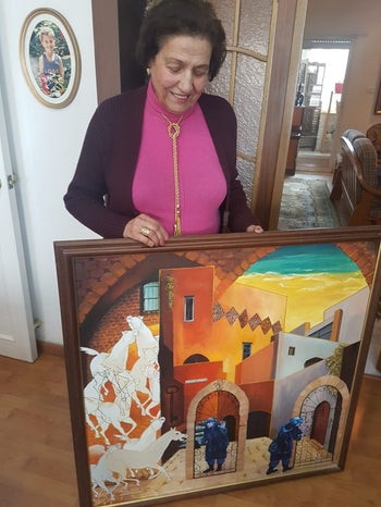 Artist Tamam al-Akhal with painting of her Jaffa home.