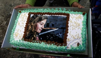 A man displaying a cake with the picture of Palestinian teen Ahed Tamimi, who is detained by Israel, during a symbolic 17th birthday party for her in the West Bank city of Hebron, January 30, 2018.