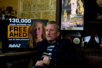 Bassem Tamimi speaking in front of a poster showing his daughter Ahed at his home in Nabi Saleh, near the West Bank city of Ramallah, January 5, 2018.