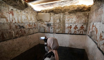 A woman takes a photo inside the tomb of an Old Kingdom priestess in Cairo that was unveiled on February 3, 2018 after being discovered during excavation work in Giza's western cemetery.