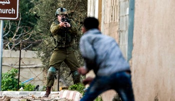 A Palestinian protester confronts an Israeli soldier during an army search operation in the Palestinian village of Burqa in the occupied West Bank, on February 3, 2018.