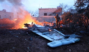A picture taken on February 3, 2018, shows a rebel fighter photographing a downed Sukhoi-25 fighter jet in Syria's northwest province of Idlib.