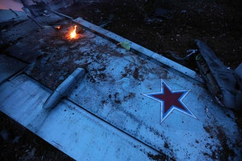 A picture taken on February 3, 2018, shows the wing of a downed Sukhoi-25 fighter jet in the the Syrian city of Saraqib, southwest of Aleppo.