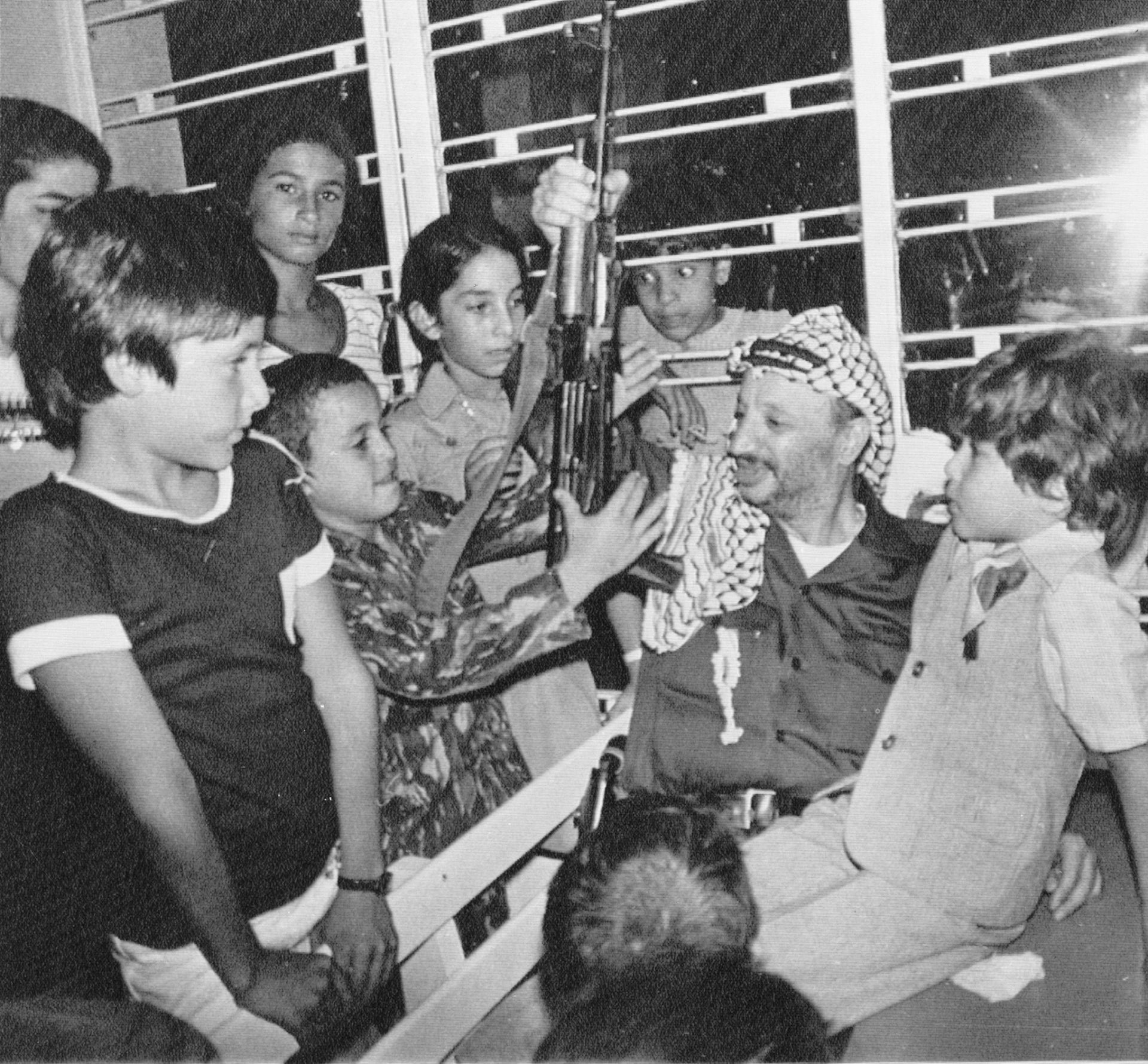 Then-PLO leader Yasser Arafat sitting with a group of refugees in a camp outside Beirut, Lebanon, August 1977.