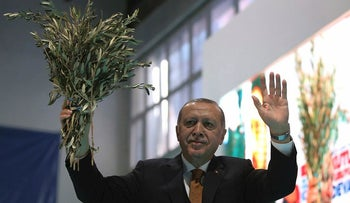 Turkey's President Recep Tayyip Erdogan holds olive branches as he addresses his party members in Batman, Turkey, Saturday, Feb. 3, 2018