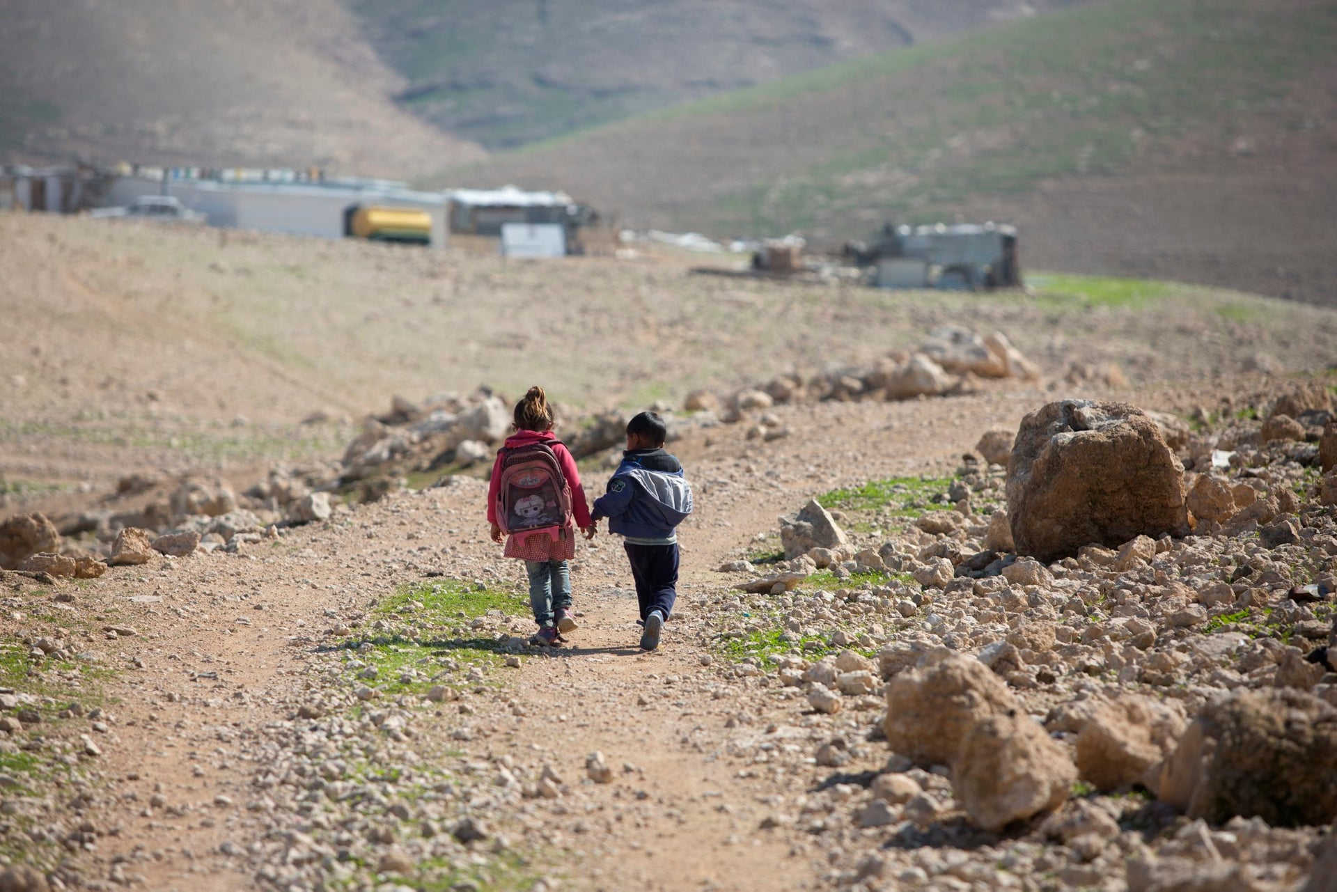 Two Bedouin children walking home from school in the West Bank village of Al Muntar, January 2018.