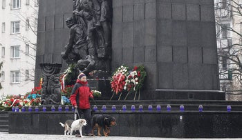 A woman walks her dogs in front of the monument to the Heroes of the Warsaw Ghetto who fought in the 1943 uprising in Warsaw, February 1, 2018.
