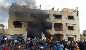 Egyptians gather at the scene following a bombing that struck a main police station in the capital of the northern Sinai province in el-Arish, Egypt, April 12, 2015.