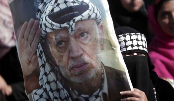 A woman holding a poster of the late PLO leader Yasser Arafat during a rally marking the 13th anniversary of his death, in Gaza City, November 2017.