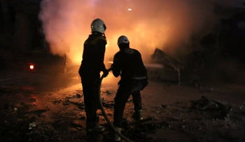 Syrian White Helmet civil defense workers extinguishing fire following a bombing in Idlib, Syria. January 7, 2018.