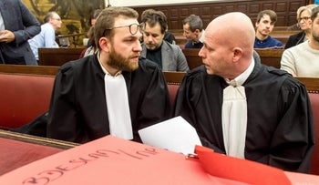 """Belgian lawyers representing Paris attacks suspect Salah Abdeslam Sven Mary (R) and Romain Delcoigne speak together prior to the opening of the trial at the """"Palais de Justice"""" courthouse in Brussels, on February 5, 2018."""