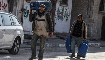Palestinians carrying gas canisters walk down a street in the Rafah refugee camp in the southern Gaza Strip, February 4, 2018.