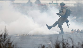 An Israeli soldier kicks a teargas canister during a protest near the West Bank city of Ramallah.