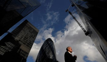 A worker walks past office skyscrapers in the City of London financial district, London, Britain, January 25, 2018.