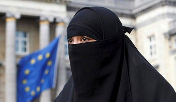 Salma, a 22-year-old French national living in Belgium who chooses to wear the niqab after converting to Islam, gives an interview to Reuters television outside the Belgian Parliament in Brussels April 26, 2010