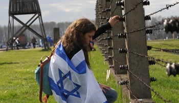 A woman, wrapped in an Israeli flag, stands in front of barbed wire at the Auschwitz-Birkenau Nazi death camp, as people take part in the annual 'March of the Living,' in Oswiecim, April 19, 2012.
