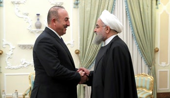 President Hassan Rohani greets Turkish Foreign Minister Mevlut Cavusoglu at the start of their meeting at the presidency office, in Tehran, Iran February 7, 2018.