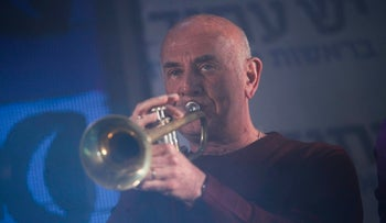 Jacob Perry playing the trumpet at a Yesh Atid party event