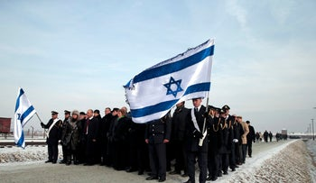 Members of a Knesset delegation stand in front of former Auschwitz-Birkenau concentration camp, January 27, 2014