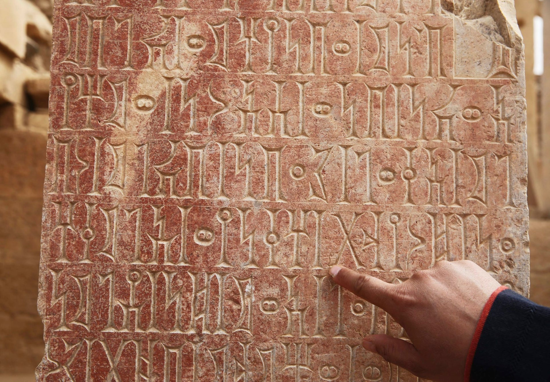 An official points to ancient South Arabian script at the Awwam Temple, also known as the Mahram Bilqis, in Marib, Yemen, Feb. 3, 2018.