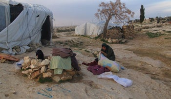 Iman Nawaja, 38, was busy moving piles of clothes out of her home.