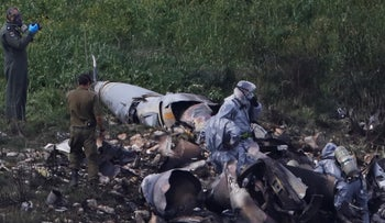 Israeli security forces examine the remains of an F-16 Israeli war plane near the village of Harduf, Israel February 10, 2018.