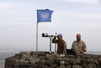 UN soldiers look out on a post at Mount Avital, in the Golan Heights near the Israeli Syrian border, February 10, 2018.