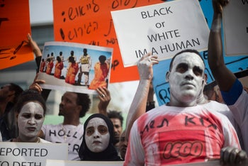 African migrants hold signs during a protest in front of the Rwandan embassy in Herzliya, Israel. Feb. 7, 2018
