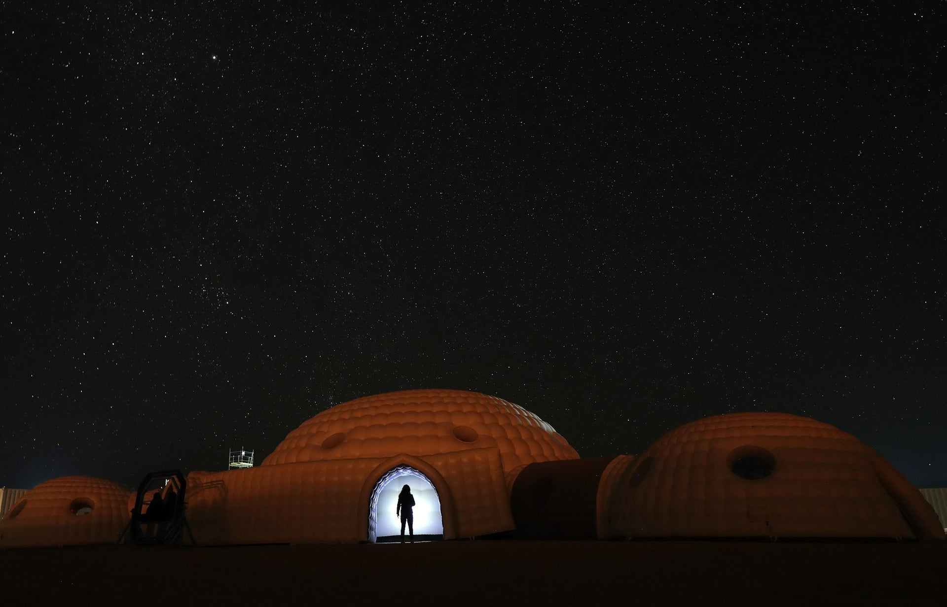 A member of the AMADEE-18 Mars simulation mission in the doorway of a simulation habitat in Oman's Dhofar desert. February 7, 2018.