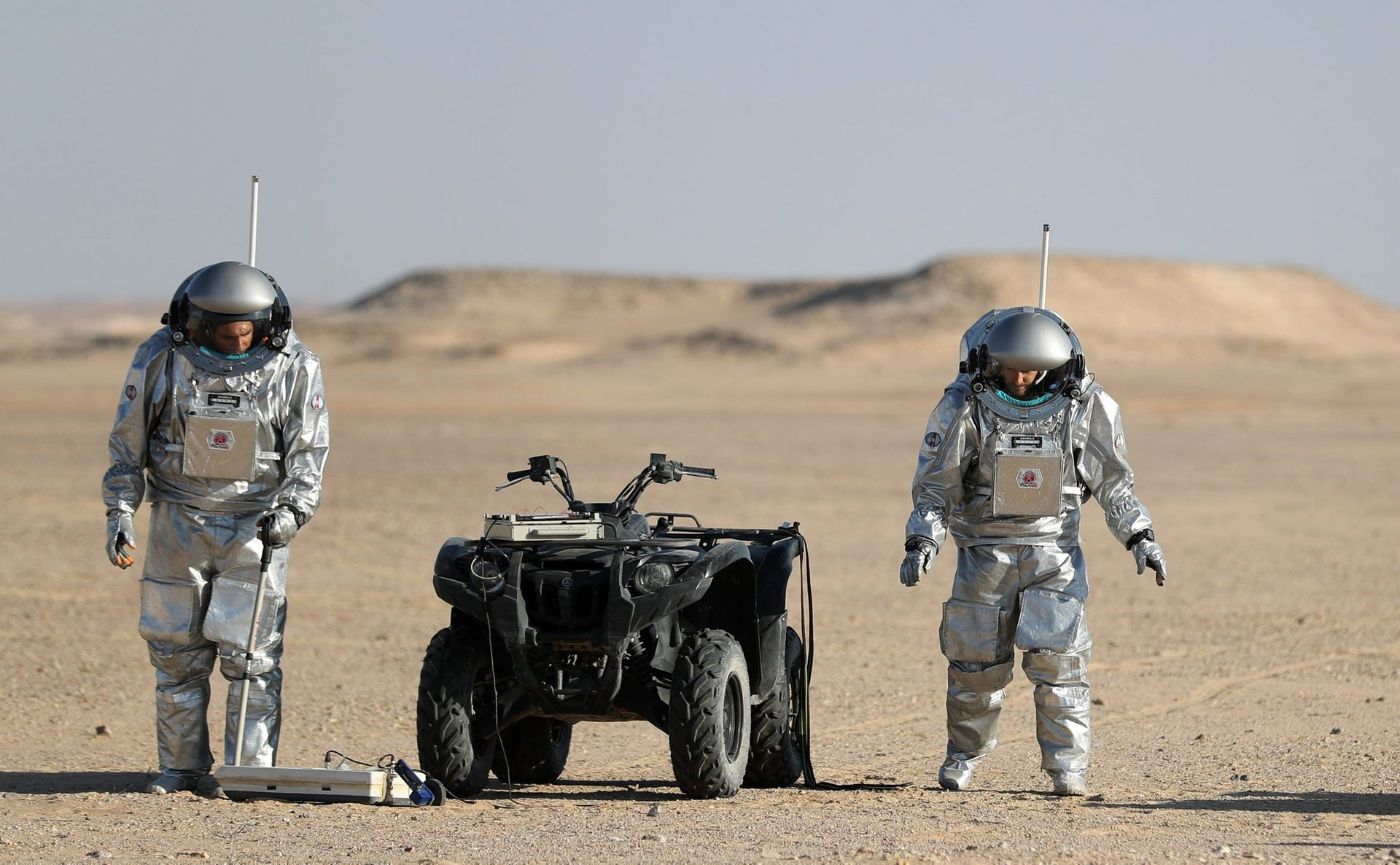 Members of the AMADEE-18 Mars simulation mission next to an all-terrain vehicle. Oman's Dhofar desert. February 7, 2018.