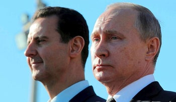 This Monday, Dec. 11, 2017 file photo, Russian President Vladimir Putin, right, and Syrian President Bashar Assad watch the troops marching at the Hemeimeem air base in Syria