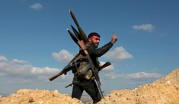 This Jan. 28, 2018 file photo, a pro-Turkey Syrian fighter waves on Bursayah hill, which separates the Kurdish-held enclave of Afrin from the Turkey-controlled town of Azaz, Syria