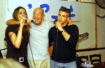 Yair Lapid, right, with singer Einat Sarouf and Hollywood producer Arnon Milchan at an Israeli nightclub in 2004.