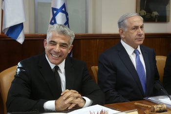 Then-Finance Minister Yair Lapid with Prime Minister Benjamin Netanyahu during a cabinet meeting in October 2014.