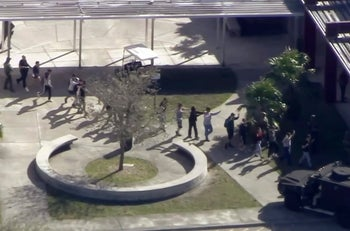 In this frame grab from video provided by WPLG-TV, students from the Marjory Stoneman Douglas High School in Parkland, Fla., evacuate, February 14, 2018.