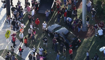 People wait for loved ones as they are brought out of the Marjory Stoneman Douglas High School after a shooting at the school that killed 17, Parkland, Florida, February 14, 2018.