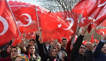 """People shout slogans awave Turkish flags during a demonstration in support of Turkish military operation in Syria, """"Operation Olive Branch"""",  during a rally in Ankara on February 14, 2018"""