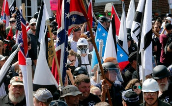 FILE - In this Saturday, Aug. 12, 2017, file photo, white nationalist demonstrators walk into the entrance of Lee Park surrounded by counter demonstrators in Charlottesville, Va.   Unease over violent white nationalist rallies in Charlottesville this summer and President Donald Trump's response loomed in the minds of many Virginia voters during Tuesday, Nov. 7 elections in which Democrats made significant gains, according to progressive advocacy groups and interviews with voters. (AP Photo/Steve Helber, File)