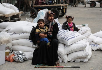 A Palestinian woman sitting with a child after receiving food supplies from the UN offices in Khan Yunis refugee camp, southern Gaza Strip, February 11, 2018.