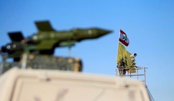 FILE PHOTO: A Hezbollah fighter stands at a watch tower at Juroud Arsal, the Syria-Lebanon border, July 29, 2017. REUTERS/Ali Hashisho/File Photo