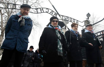 """Survivors and guests walk past the """"Arbeit Macht Frei"""" gate at Auschwitz, the former Nazi German concentration camp in Oswiecim, Poland, January 27, 2018."""