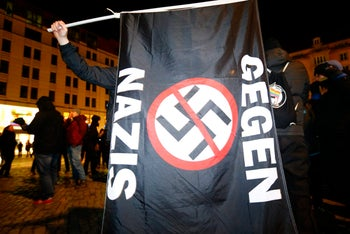 """A person holds a flag reading """"No Nazis"""" as they protest against the anti-immigrant Alternative for Germany Party (AfD) in Dresden, Germany, February 13, 2018."""