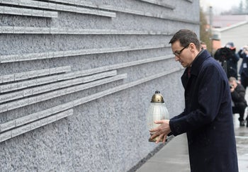 Polish Prime Minister Mateusz Morawiecki places a candle at a memorial wall with names of Poles who saved Jews during the Holocaust.